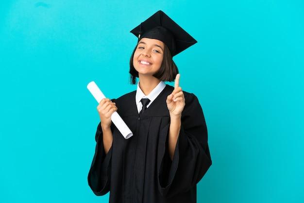 고립 된 파란색 배경 위에 손가락을 보여주고 들어 올리는 젊은 대학 대학원 소녀