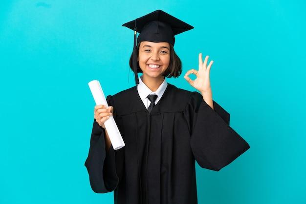 指でokサインを示す孤立した青い背景の上の若い大学卒業生の女の子