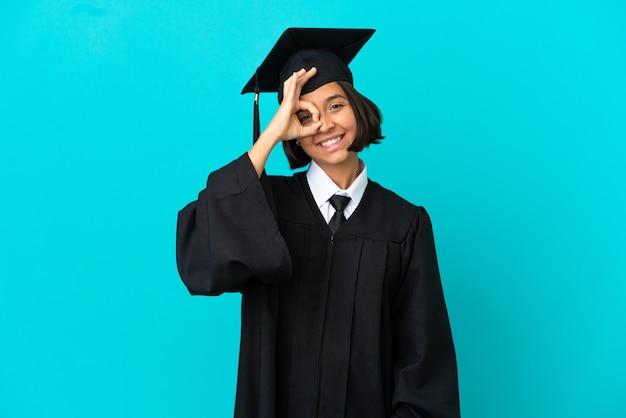 Молодая выпускница университета на изолированном синем фоне, показывая пальцами знак ок