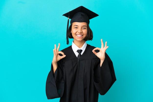 두 손으로 확인 표시를 보여주는 고립 된 파란색 배경 위에 젊은 대학 대학원 소녀