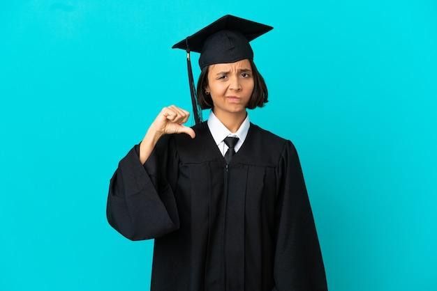 부정적인 표정으로 엄지손가락을 아래로 보여주는 고립 된 파란색 배경 위에 젊은 대학 대학원 소녀