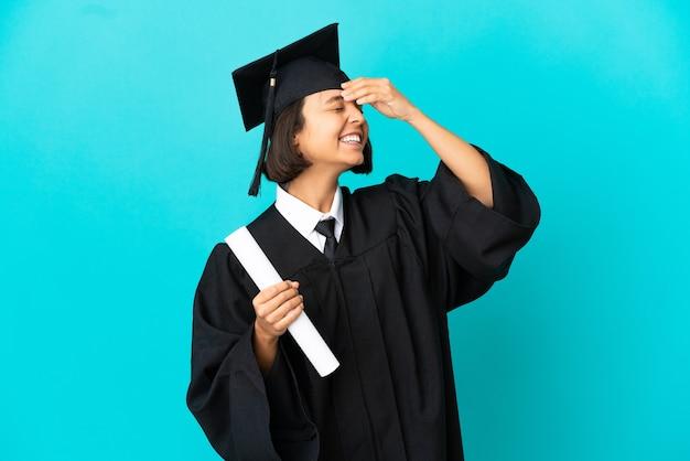 たくさん笑って孤立した青い背景の上の若い大学卒業生の女の子