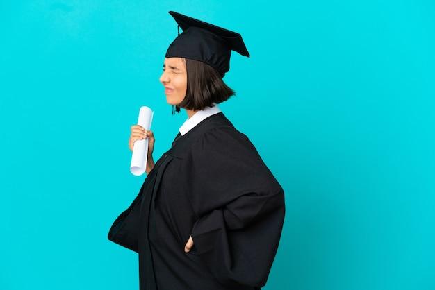 노력을 했다는 이유로 요통으로 고통받는 고립된 파란색 배경 위에 있는 젊은 대학 대학원생