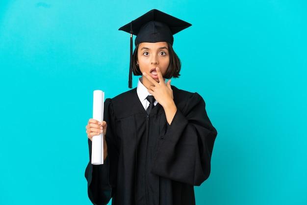 격리된 파란색 배경 위에 있는 젊은 대학 대학원 소녀는 오른쪽을 바라보는 동안 놀라고 충격을 받았습니다.
