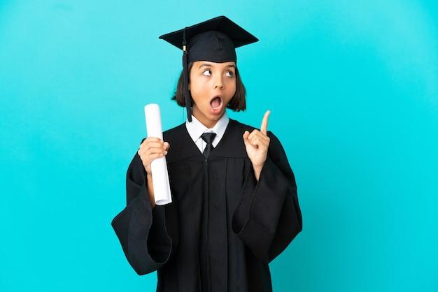 Молодая девушка-выпускница университета на изолированном синем фоне думает о идее, указывая пальцем вверх