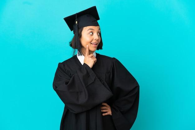 고립 된 파란색 배경 위에 젊은 대학 대학원 소녀는 찾는 동안 아이디어를 생각