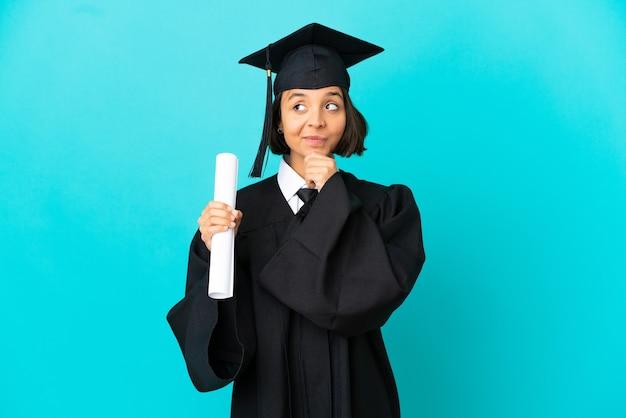 Девушка-выпускница университета на изолированном синем фоне думает