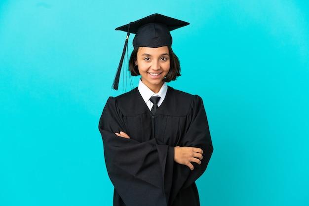 Молодая девушка-выпускница университета на изолированном синем фоне со скрещенными руками и нетерпением ждет