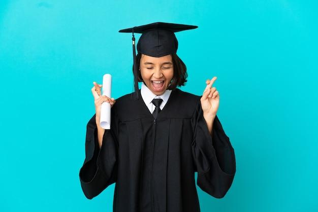 손가락 횡단과 고립 된 파란색 배경 위에 젊은 대학 대학원 소녀