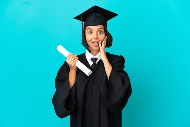 놀라움과 충격을 받은 표정으로 고립된 파란색 배경 위에 젊은 대학 대학원 소녀