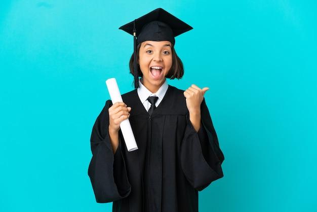 고립된 파란색 배경 위에 엄지손가락을 치켜세우고 웃는 젊은 대학 대학원생