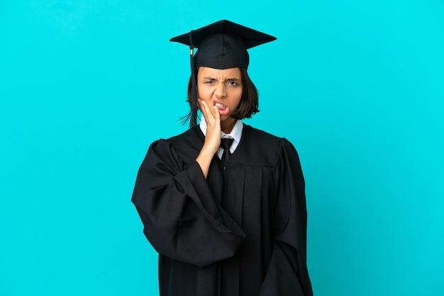 Молодая выпускница университета на изолированном синем фоне с зубной болью