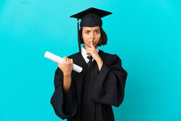 외진 파란 벽 너머로 옆을 가리키고 침묵의 몸짓을 하는 젊은 대학 대학원생