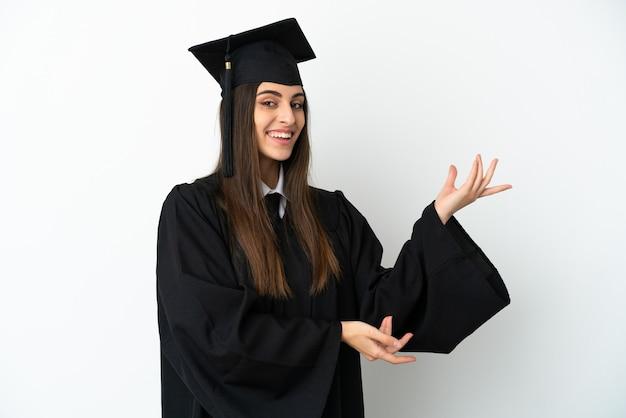흰색 배경에 격리된 젊은 대학 졸업생은 초대하기 위해 손을 옆으로 뻗어
