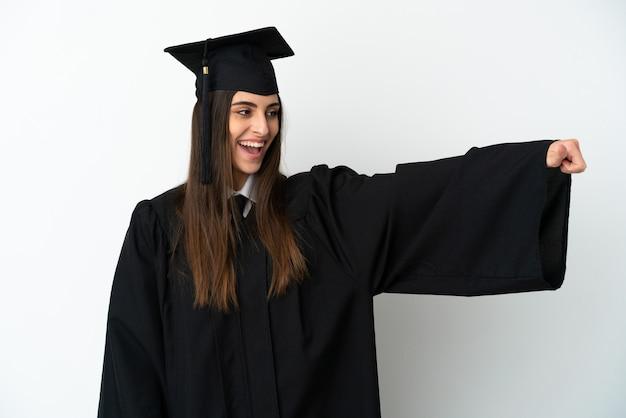 Молодой выпускник университета изолирован на белом фоне, показывая большой палец вверх жест