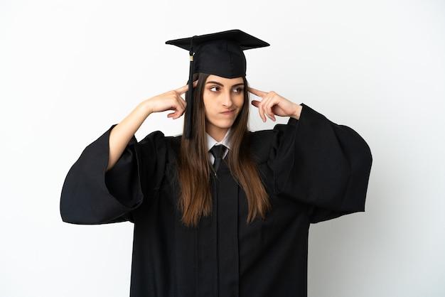 의심과 생각을 가진 흰색 배경에 고립 된 젊은 대학 졸업