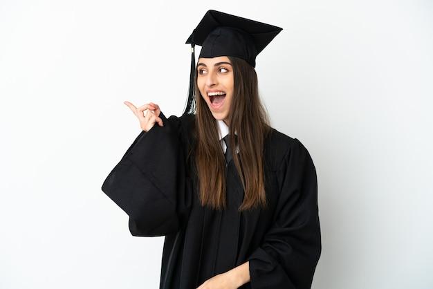 Молодой выпускник университета изолирован на белом фоне, намереваясь реализовать решение, подняв палец вверх