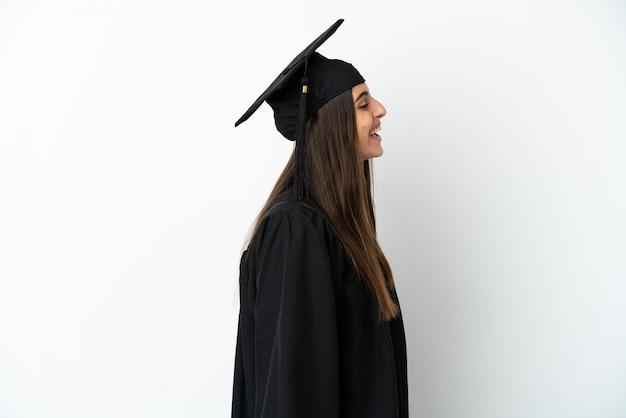 Молодой выпускник университета, изолированные на белом фоне, смеясь в боковом положении