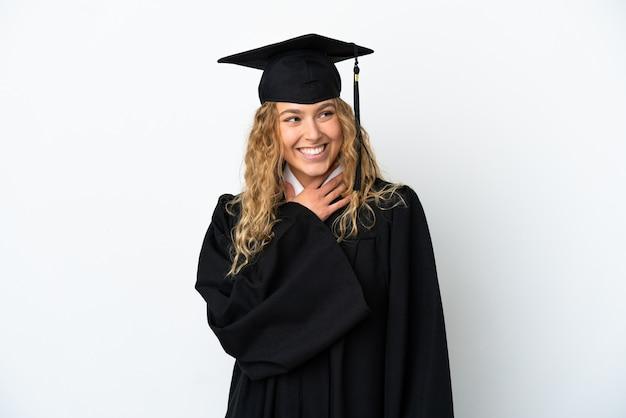 Молодой выпускник университета, изолированные на белом фоне, глядя вверх, улыбаясь