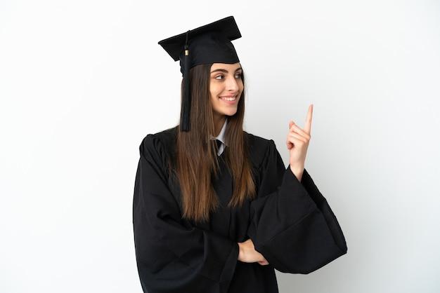 Молодой выпускник университета изолирован на белом фоне, указывая на отличную идею