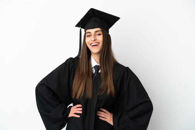 Молодой выпускник университета, изолированные на белом фоне, позирует с руками на бедрах и улыбается