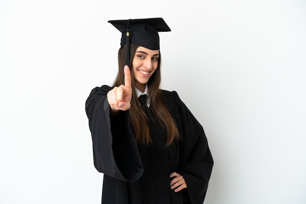 Молодой выпускник университета изолирован на белом фоне, показывая и поднимая палец