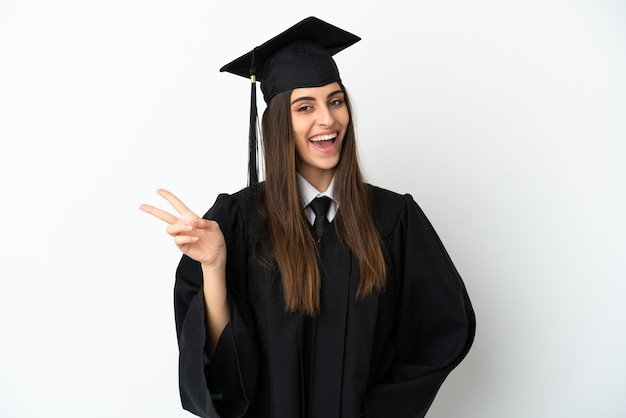 Молодой выпускник университета изолирован на белом фоне улыбается и показывает знак победы