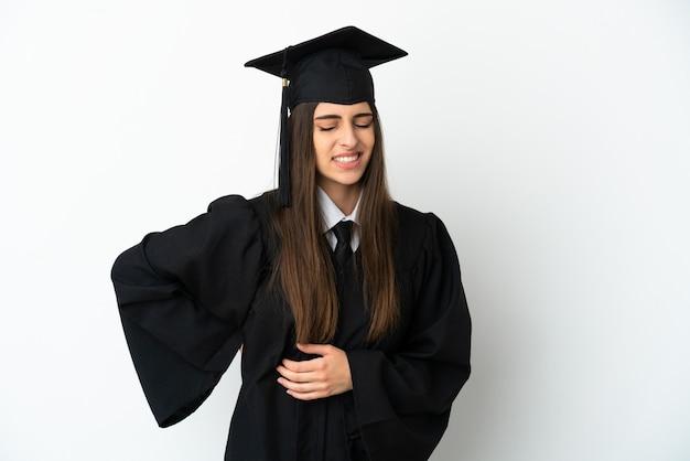 흰색 배경에 격리된 젊은 대학 졸업생은 노력을 했다는 이유로 요통으로 고통받고 있다
