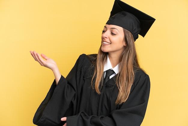 노란색 배경에 격리된 젊은 대학 졸업생이 초대하기 위해 손을 옆으로 내밀었습니다.