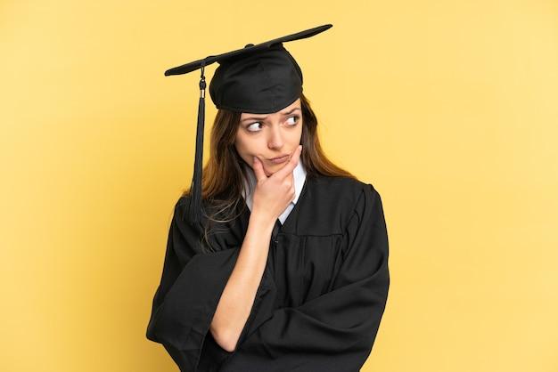 Молодой выпускник университета, изолированные на желтом фоне, сомневаясь
