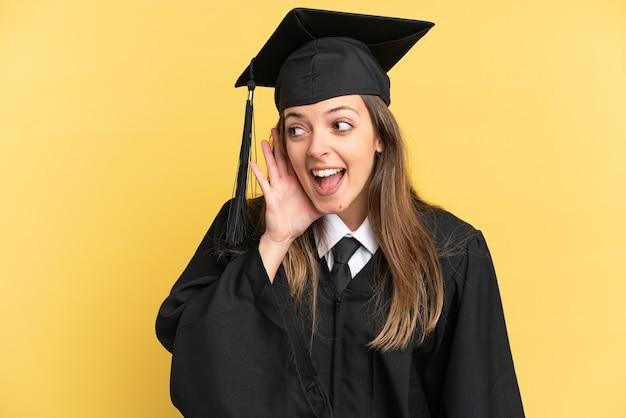 노란색 배경에 격리된 젊은 대학 졸업생은 귀에 손을 대고 무언가를 듣고 있습니다.