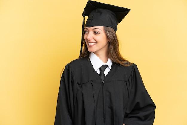 노란색 배경 찾고 측면에 고립 된 젊은 대학 졸업