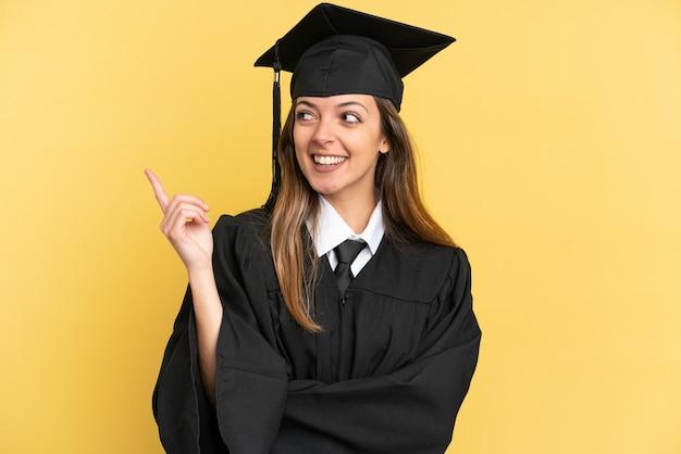 좋은 아이디어를 가리키는 노란색 배경에 고립 된 젊은 대학 졸업생