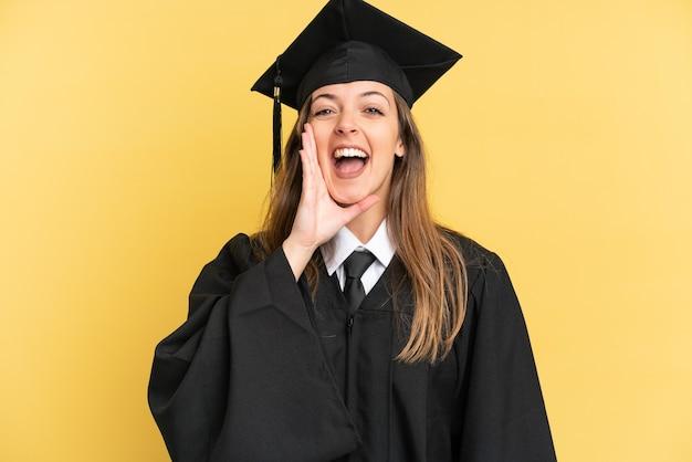 노란 배경에 격리된 젊은 대학 졸업생이 입을 크게 벌리고 소리쳤다