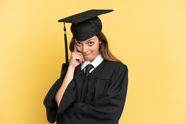 Молодой выпускник университета изолирован на желтом фоне, думая об идее