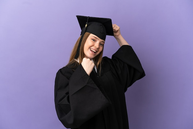 Young university graduate over isolated purple background celebrating a victory