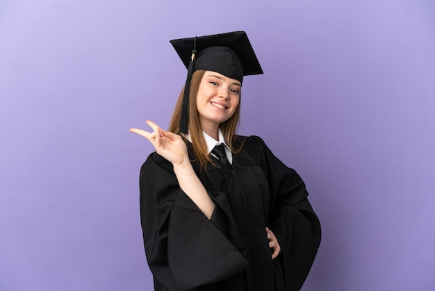 Young university graduate over isolated purple background smiling and showing victory sign