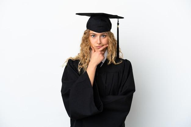 Young university graduate isolated on white background thinking