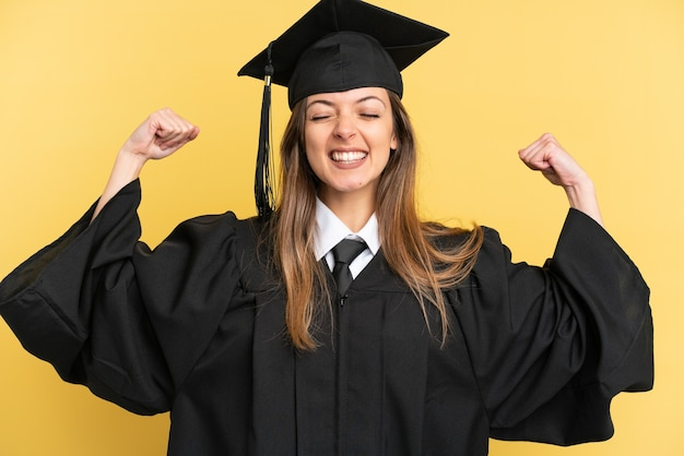 Young university graduate isolated on yellow background doing strong gesture