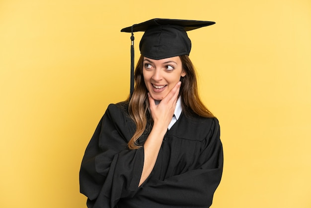 Young university graduate isolated on yellow background looking up while smiling