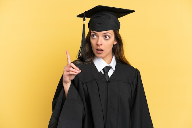 Young university graduate isolated on yellow background thinking an idea pointing the finger up