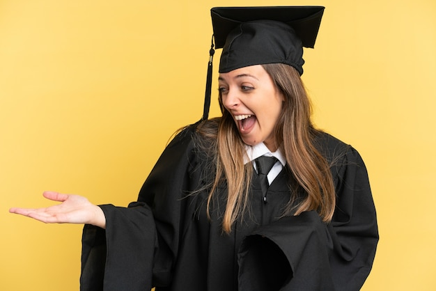 Young university graduate isolated on yellow background with surprise expression while looking side