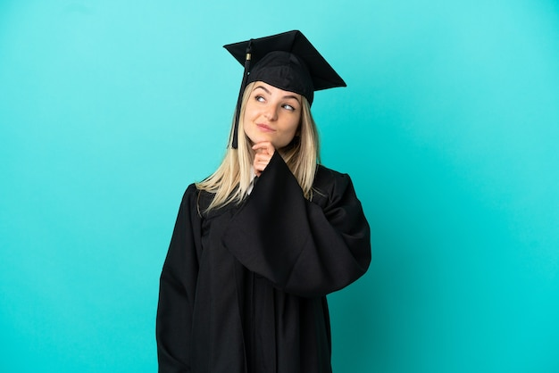 Молодой выпускник университета на изолированном синем фоне и смотрит вверх