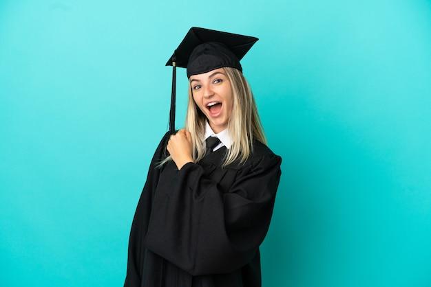 승리를 축하하는 고립된 파란색 배경 위에 젊은 대학 졸업