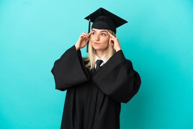 의심과 생각을 가진 고립 된 파란색 배경 위에 젊은 대학 졸업