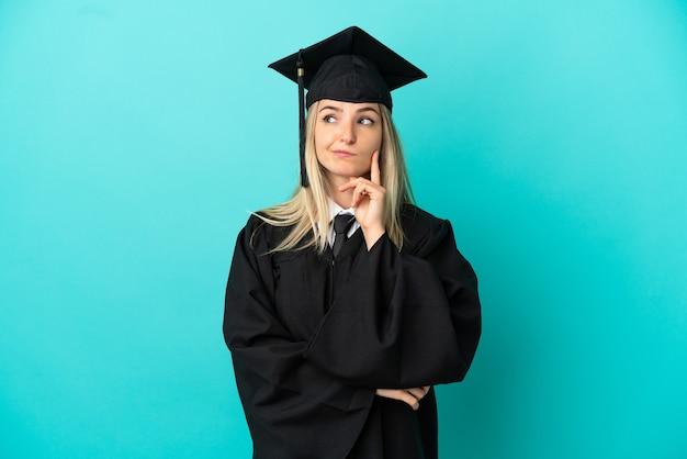 Молодой выпускник университета на изолированном синем фоне с сомнениями и мышлением
