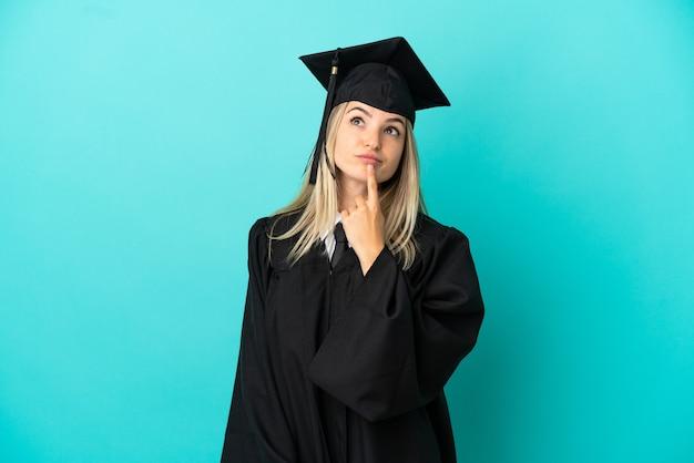 Молодой выпускник университета на изолированном синем фоне сомневается, глядя вверх