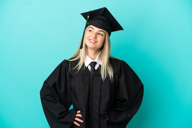 고립된 파란색 배경 위에 팔짱을 끼고 웃고 있는 젊은 대학 졸업