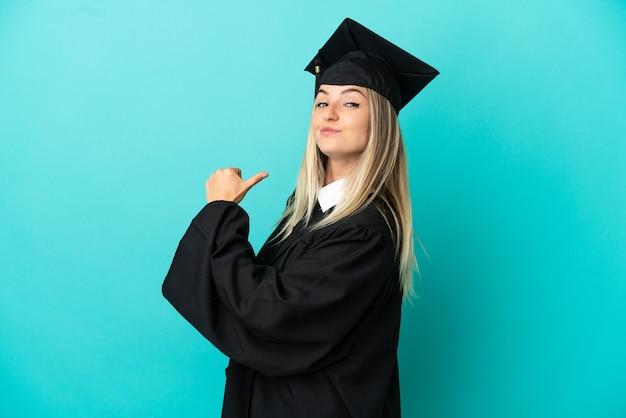 고립된 파란색 배경 위에 자랑스럽고 자기 만족스러운 젊은 대학 졸업