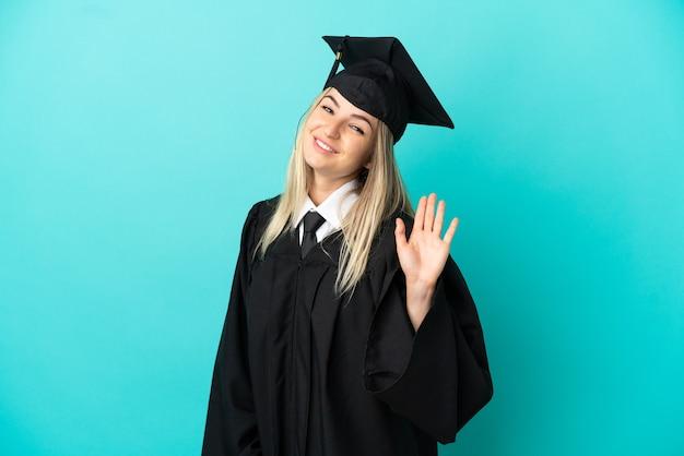 Молодой выпускник университета на изолированном синем фоне салютует рукой со счастливым выражением лица